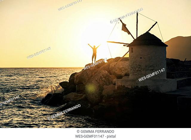 Greece, Amorgos, Aegialis, silhouette of man with arms raised near wind mill at sunset