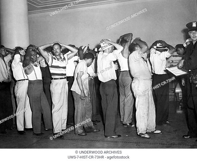Detroit, Michigan: June 24, 1943 Blacks under arrest being booked into jail by a white police officer in the aftermath of the three days of riots over wartime...