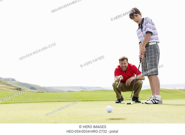 father coaching pre-teen son on putting