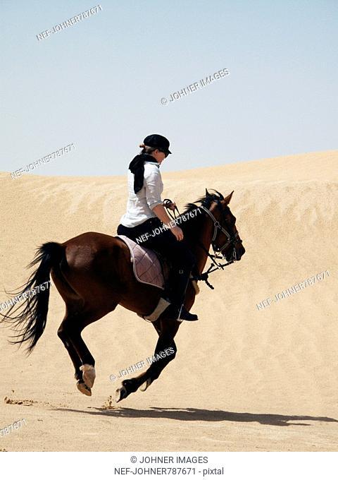 Woman riding a horse in the desert, Tunisia