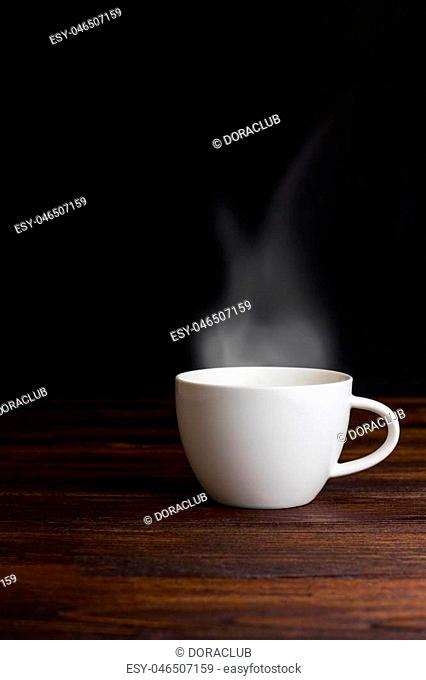 White coffee cup on plate with smoke