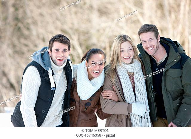 Portrait of smiling couples in snow