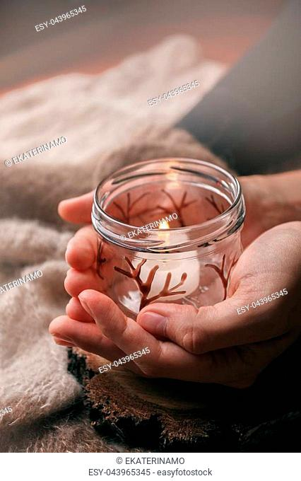 Still life details of living room. A burning candle in the female hands. Autumn weekend concept. Fall home decoration