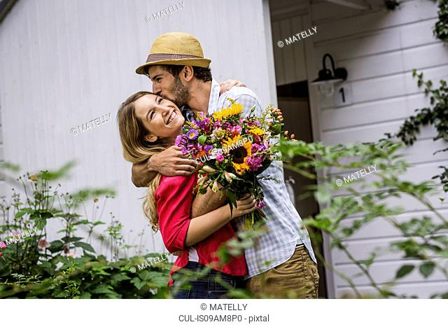 Young couple with bunch of flowers hugging in garden