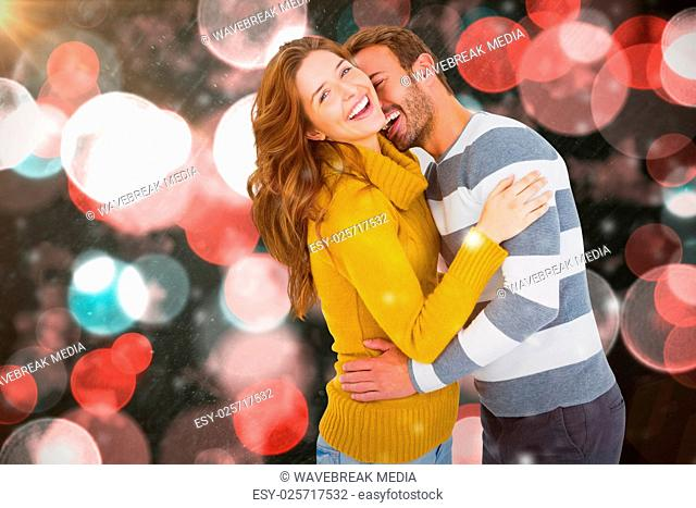 Composite image of happy young couple cuddling