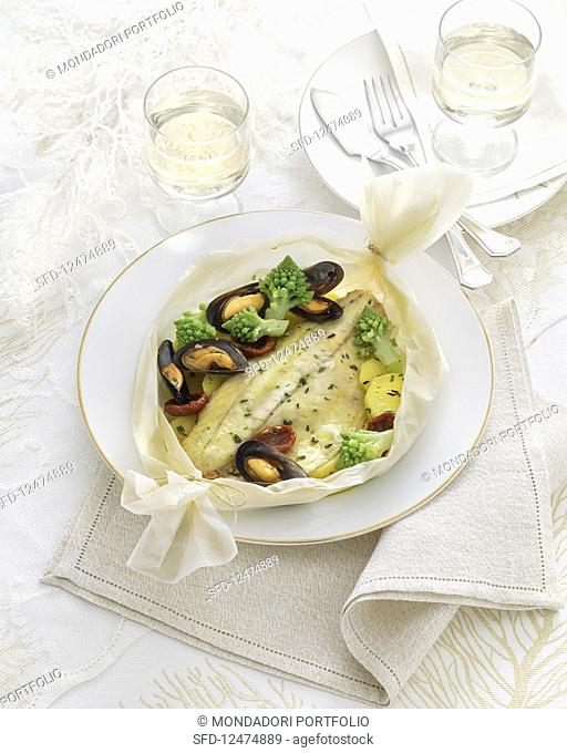 Fish fillet in a white wine broth with mussels and Romanesco in parchment paper