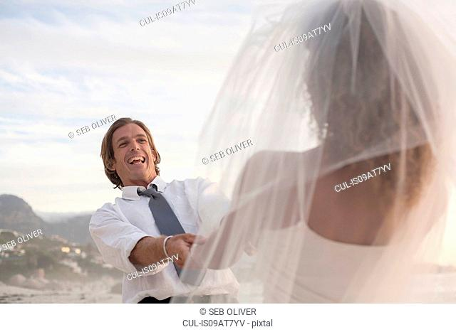 Bride and groom on beach, holding hands, fooling around, laughing