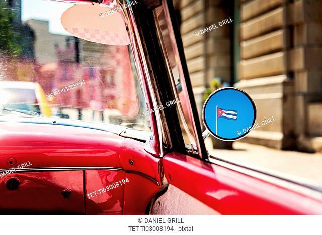 Cuba, Havana, Cuban flag reflecting in mirror of convertible