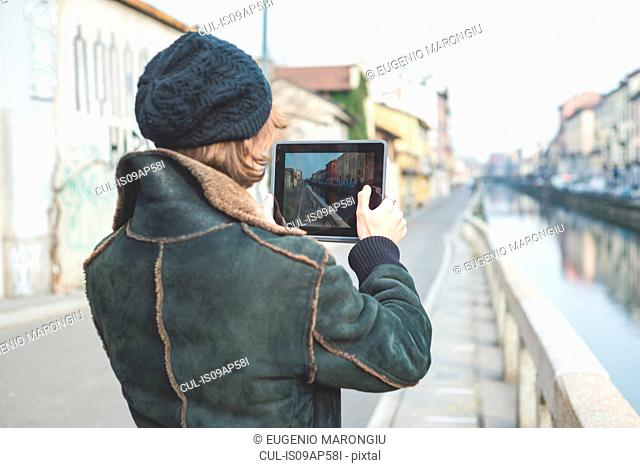 Man taking photograph of canal with digital tablet, Milan, Italy