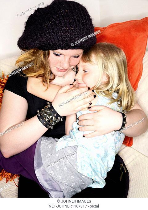 Teenage girl embracing little sister