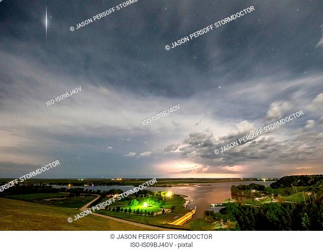 Thunderstorm roars in the distance while a satellite flashes light off its solar panels over rural Nebraska , US