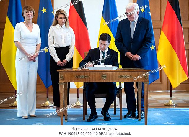 18 June 2019, Berlin: Volodymyr Selensky (2nd from right), President of Ukraine, signs the guest book in the presence of his wife Olena Selenska (2nd from left)...