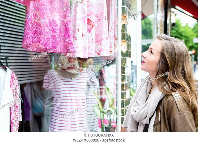 Germany, young woman looking at clothes in window display