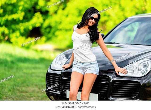 Portrait of beautiful brunette woman standing near the car hood