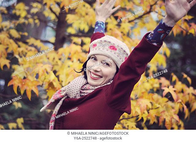 Happy mid adult woman with raised arms, autumn