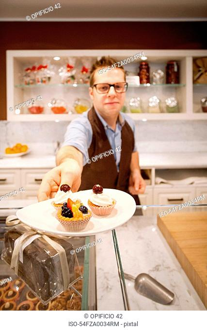 Cashier holding plate of tarts in bakery