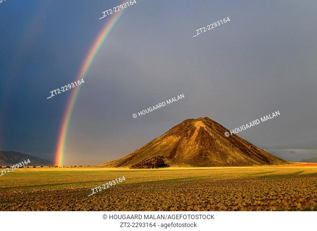 Landscape photo of a rainbow over a mountain at sunset. Namib Rand, Namibia