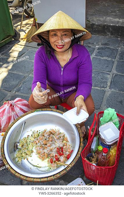 Woman selling rice paper wraps of fish and chicken from a street kitchen, Hoi An, Vietnam, Asia