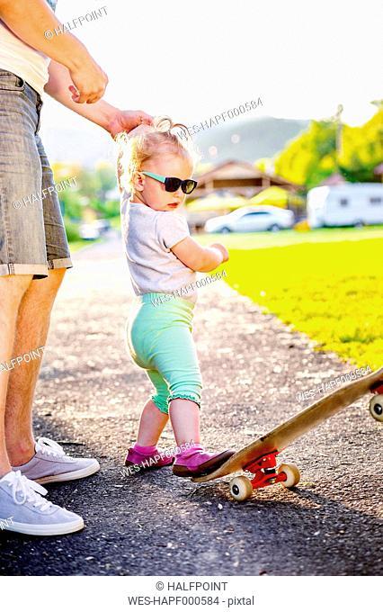 Portrait of toddler girl wearing sunglasses kicking skateboard