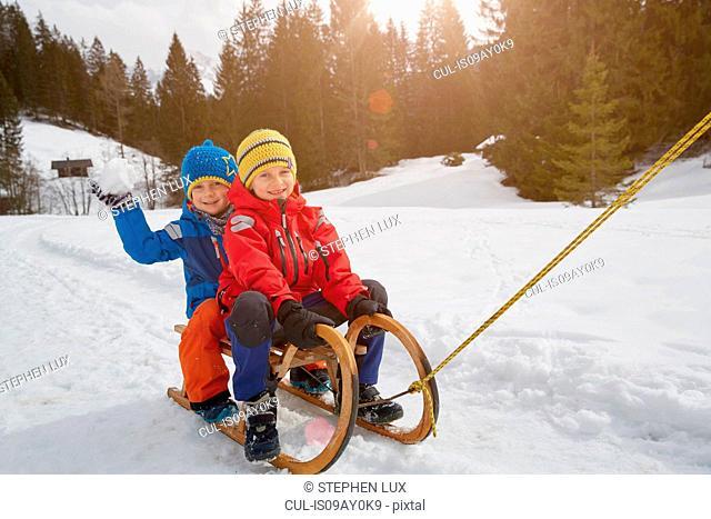 Boy and brother being pulled on toboggan in snow, Elmau, Bavaria, Germany