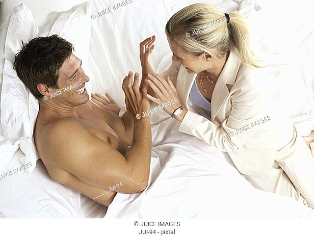 Couple laughing and joking in bed, side view, elevated view