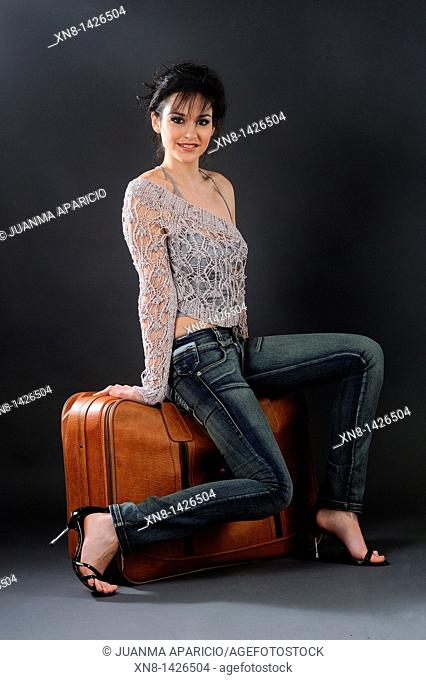 young woman photographed in full length studio, sitting on a leather suitcase in a carefree, smiling at the camera