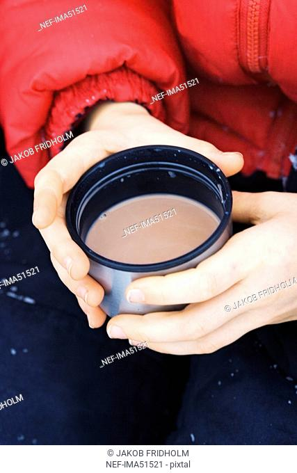 A child holding a cup of hot cocoa, Sweden