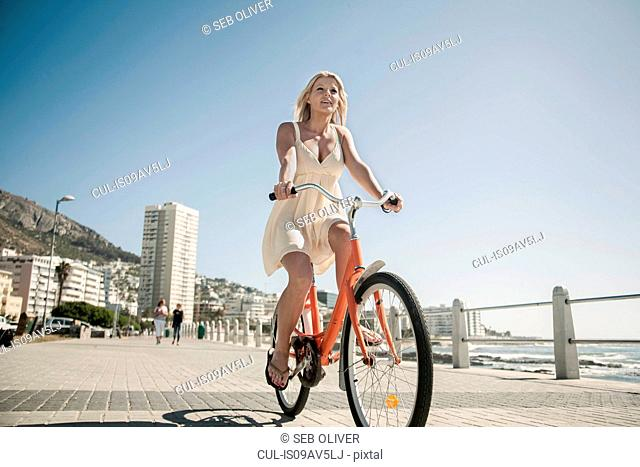 Young woman cycling on seafront, Cape Town, South Africa