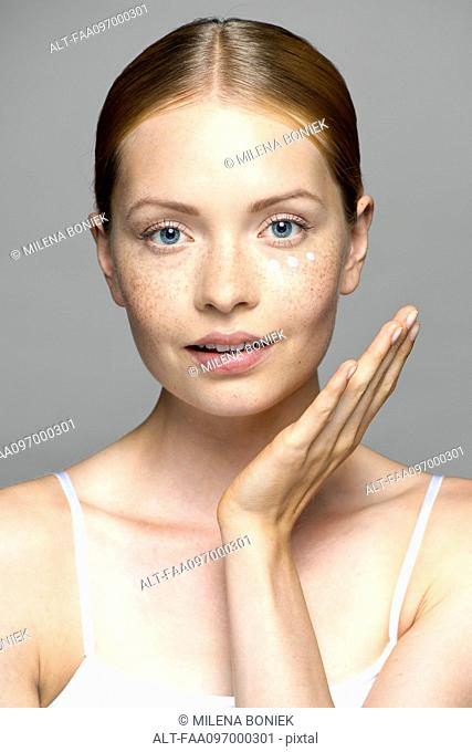 Young woman applying moisturizer to face