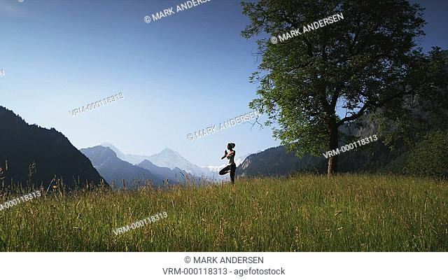 woman practicing yoga in a mountain field
