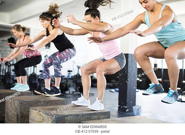 Determined women doing jump squats on boxes in exercise class