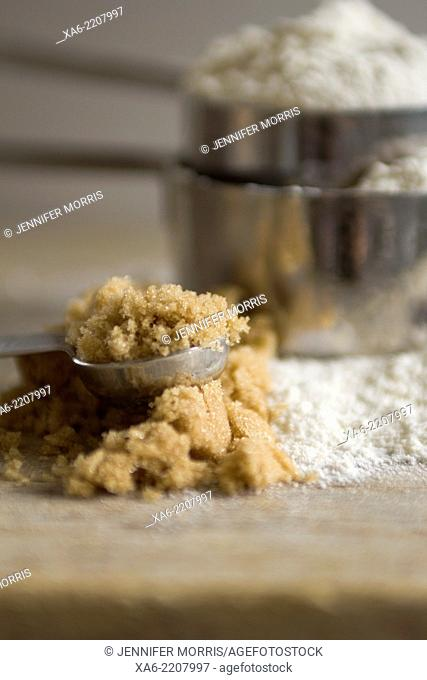 Brown sugar spills out of a measuring spoon with stacked measuring cups of flour in the background