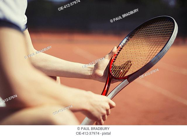 Young male tennis player holding tennis racket