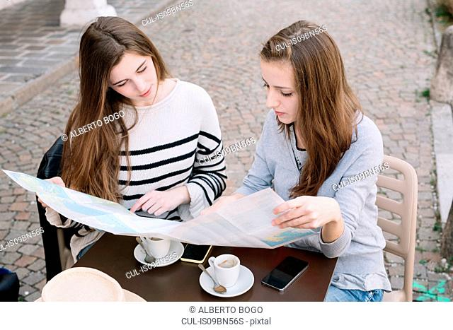 Girlfriends reading street map at cafe