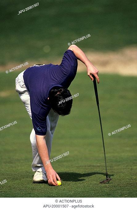 Golfer retrieves his golf ball