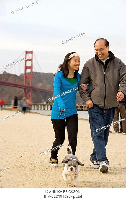 Chinese father and daughter walking dog