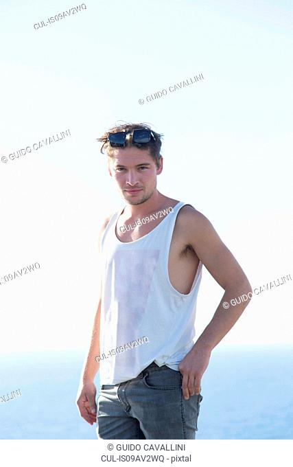 Young man in vest wearing sunglasses on head looking at camera smiling, Capo Caccia, Sardinia, Italy