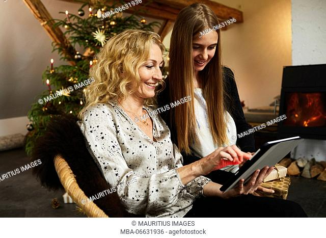 Mother and daughter with laptop in front of Christmas tree