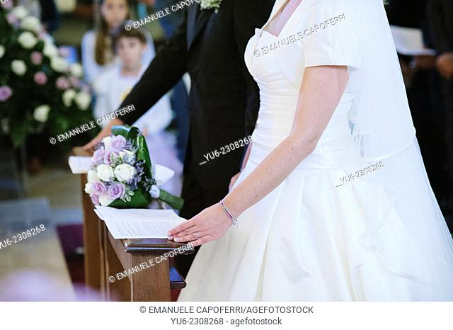 Hands of the newlyweds during Mass