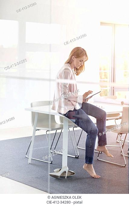 Barefoot businesswoman using digital tablet in conference room