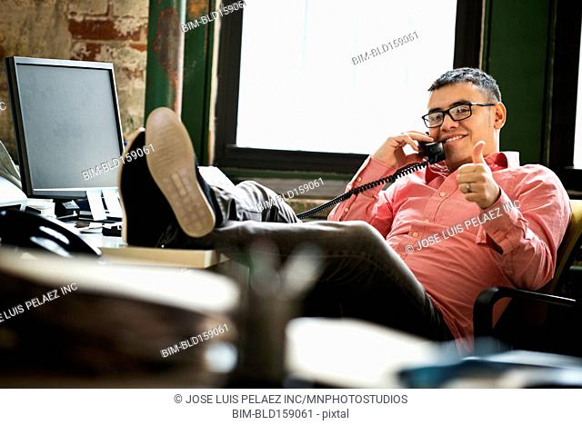 Hispanic businessman giving thumbs up on telephone at office desk