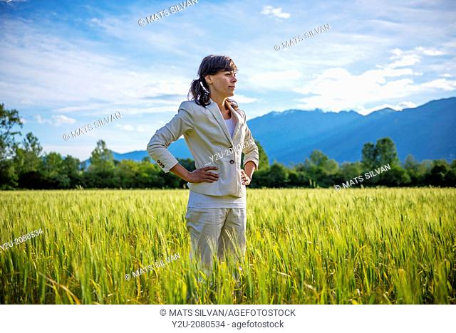 Proud woman standing up on a wheat field with mountain in background in ticino switzerland
