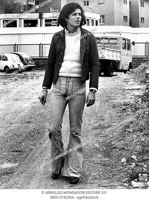 Claudio Baglioni (Claudio Enrico Paolo Baglioni), the Italian singer-songwriter, walking along an unpaved road. Rome (Italy), 1974