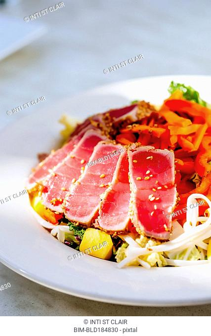 Plate of sliced tuna and salad