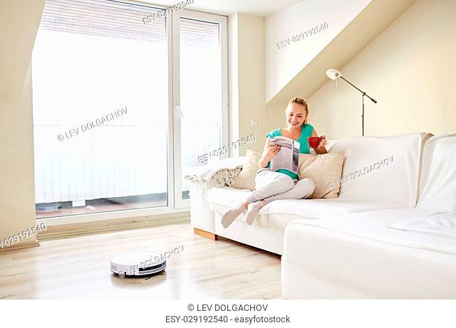 people, housework and technology concept - happy woman reading magazine and drinking coffee while robot vacuum cleaner at home
