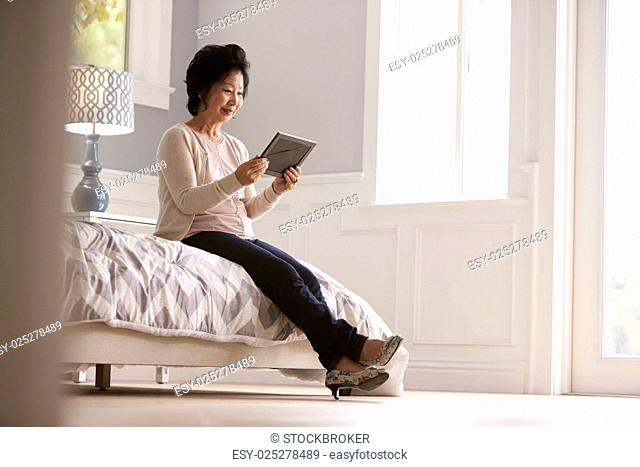 Senior Woman Sitting On Bed Looking At Photo Frame