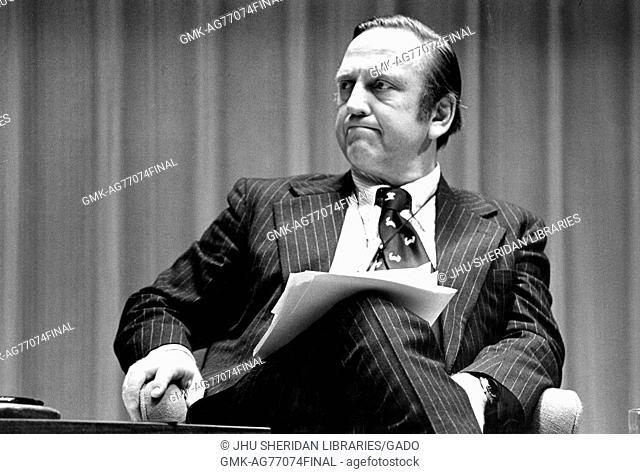 A portrait of Congressman John Brademas looking unamused sitting on stage at American University Symposium, Washington DC, February 21, 1976