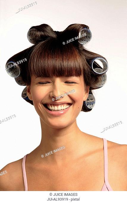 Happy woman wearing hair curlers