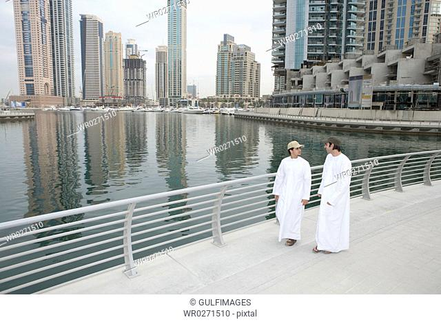 Friends conversing with sea and buildings in background