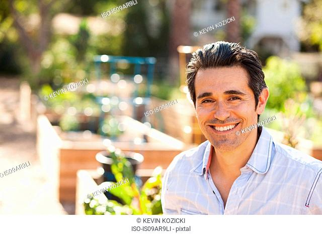 Portrait of mid adult man in community garden